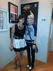 Two girls posing in front of art at an art show