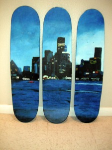 skateboards with a painting of a city at night